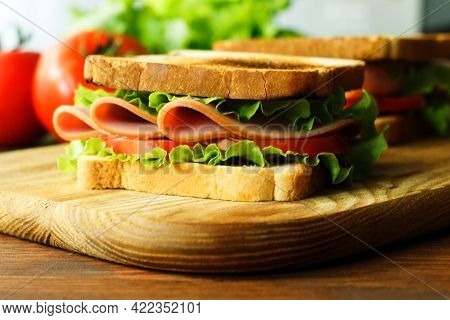Smoked Turkey Sandwich With Ham, Tomatoes, Lettuce, On Wooden Background