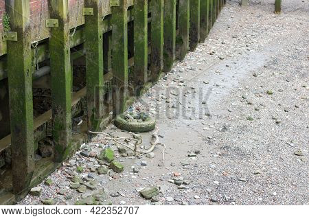 Dried River Bed With Old Discarded Tyre And Wooden Pier Supports