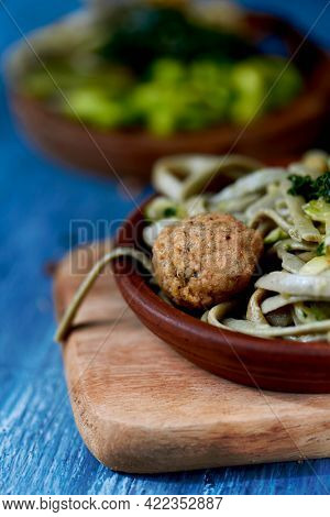 closeup of a dish with some vegan meatballs, spelt tagliatelle and kale on a blue rustic wooden table, next to another dish with edamame beans, spelt tagliatelle, tofu, kale and shiitake mushrooms