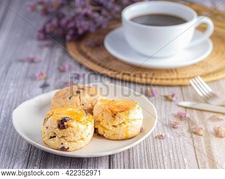 Side View Of Traditional British Scones And Cookie With A White Coffee Cup And Flower Blurred Backgr