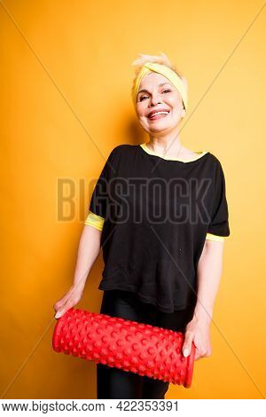 Cute Elderly Woman In Black T-shirt Smiles And Holds Fascia In Her Hands While Looking At The Camera