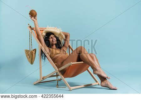 Black woman in straw hat smiling while sitting in chaise lounge isolated over blue background