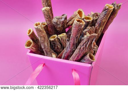 A Beautiful Pink Box Of Pet Treats. Dried Dental Goodies For Dogs On A Pink Background. Delicious Re
