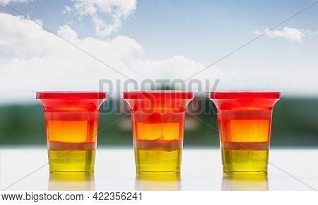Three Glasses Of Colorful Striped Jelly On A Natural Background. Rainbow Jelly For Kids Party. Close