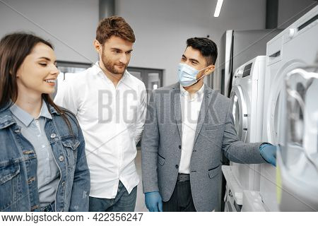 Salesman In Hypermarket Wearing Medical Mask Demonstrates His Clients A New Washing Machine