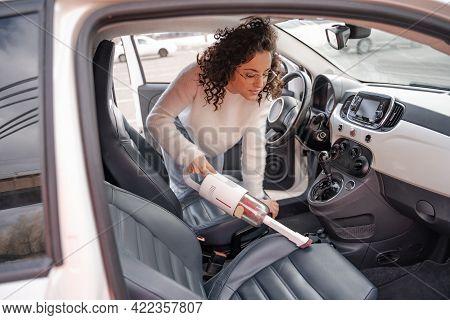 Girl Vacuuming Car Seat With Vacuum Cleaner In Car