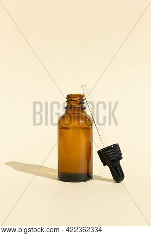 A Glass Bottle With A Pipette For Essential Oil, Lotion Or Serum On A Pastel Beige Background. Dark