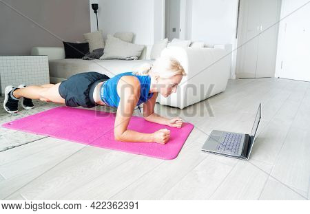 Active Slender Woman Doing Sport In Living Room, Standing In Plank Pose On Yoga Mat And Watching Onl