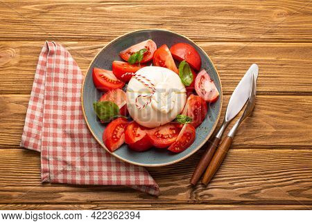Italian Salad With Fresh Tomatoes, Burrata Cheese, Basil And Olive Oil Served On Ceramic Plate On Ru