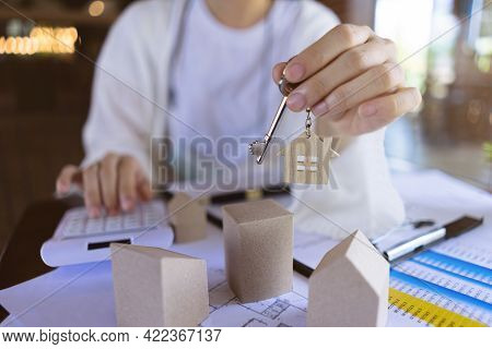 Professional Real Estate Agents Showing House Keys And Calculate The Price Of House To Customers Wit