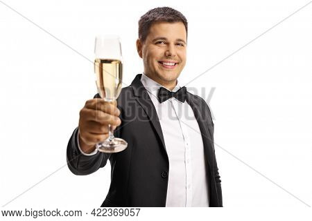 Elegant young man in a suit and bow tie toasting with a glass of sparkling wine isolated on white background