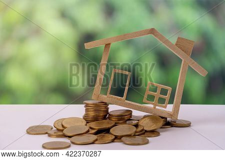 Miniature Wood House Model On Stack Money Coin And Background Eco. Home Eco And Real Estate Concept.