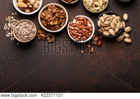 Selection Of Assorted Raw Nuts And Various Seeds In Bowls On Brown Stone Background From Above, Heal