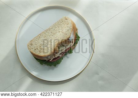 Chicken Salad Sandwich With Lettuce On Whole Wheat Bread Sliced On A Plate.