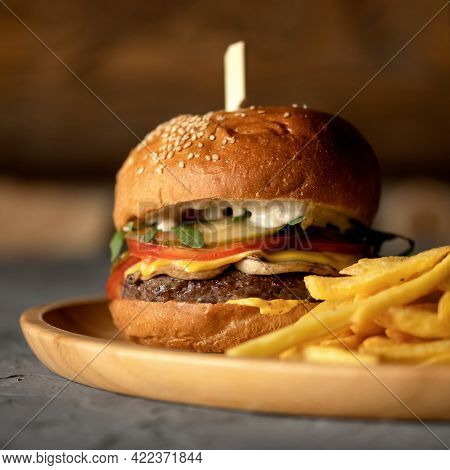 Classic American Fast Food Menu. Close Up Of French Fries And Big Cheeseburger On Blurred Background