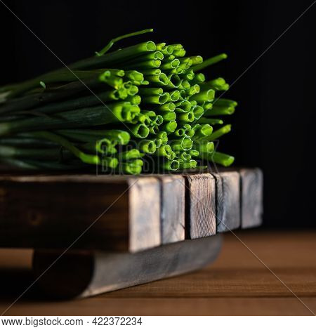 Juicy Fresh Green Onions On Cutting Board. Fresh Greens Backlit By Sunlight On Wooden Background. So