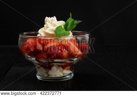 Strawberry with cream decorated with mint leaf on black wooden background, with copyspace, food and drink concept