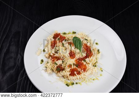 Pasta with red caviar parmesan cheese and basil. The concept of Italian cuisine.
