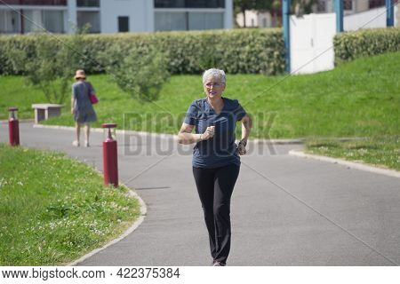 portrait of a 55 year old senior woman doing fitness in a park