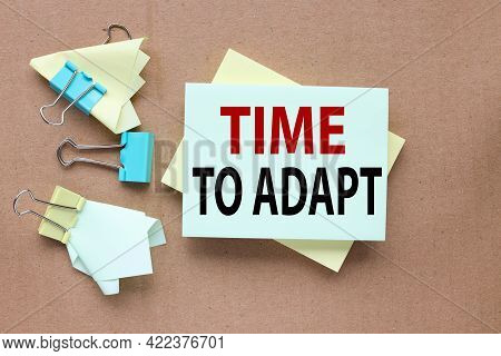 Time To Adapt. Text On Sticker On Craft Background