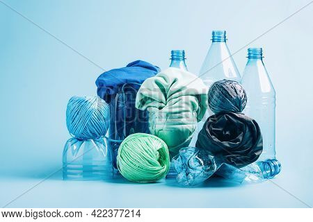 Empty Plastic Bottle And Various Fabrics Made Of Recycled Polyester Fiber Synthetic Fabric On A Blue