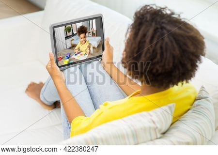 family, technology and people concept - african american mother having video call with little daughter on tablet pc computer at home