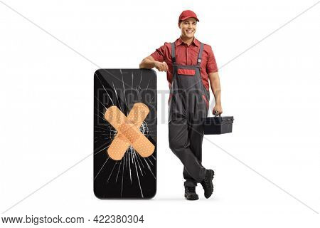 Mobile phone repair technician leaning on a smartphone with a broken screen and bandage isolated on white background
