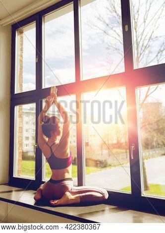 fitness, sport and healthy lifestyle concept - woman doing yoga exercise on window sill at studio