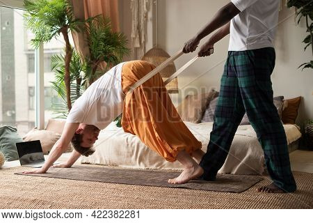 Yoga Teacher Or Pilates Instructor Helping Young Man To Stretch Muscles Doing Downward Facing Dog