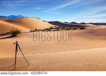 Photographic tripod prepared for evening shooting. USA. Mesquite Flat Sand Dunes, California. Light sand waves from the desert wind. Concept of active and photo tourism