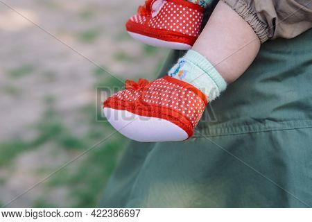 Children's Feet In Red Polka Dot Booties On A Background Of Green Grass And Mother's Khaki Dress