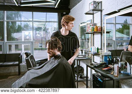 Handsome brunet man visiting hairstylist in barbershop.