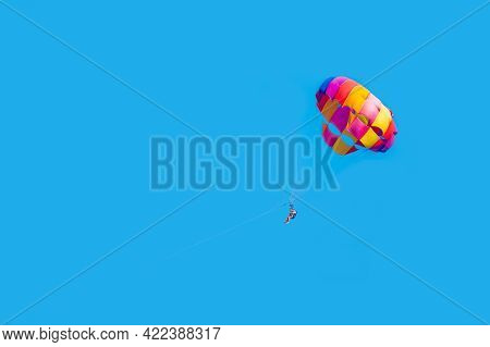 Happy Couple Parasailing On Tropical Beach In Summer. Couple Under Parachute Hanging Mid Air. Positi
