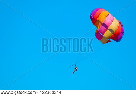 Parasailing On Blue Sky. Couple Under Parachute Hanging Mid Air. Positive Human Emotions, Feelings,