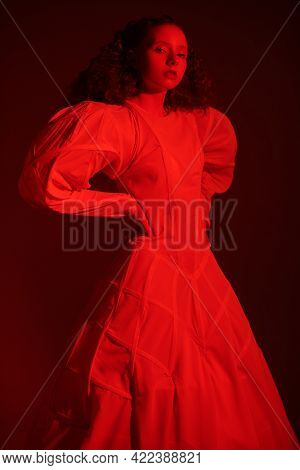 Portrait of a sophisticated female model with lush red curly hair posing in a white art dress in red light. Fashion art. Studio shot.