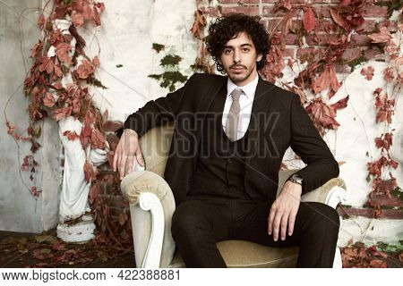 Handsome brunet man in elegant classic suit and a tie sits in an armchair on a vintage background. Men's fashion.