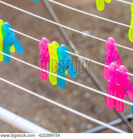 Colorful Plastic Clothes Pegs On Empty Metal Clothes Dryer.
