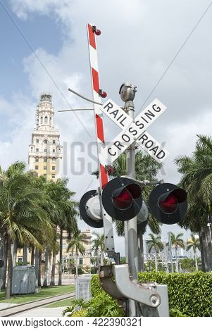The Open Railroad Crossing Barrier And Miami Historic Freedom Tower In A Background (florida).