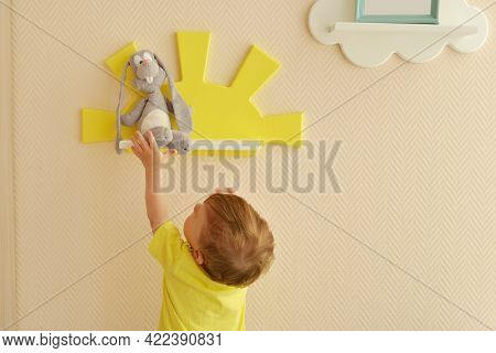 Stylish And Modern Interior Design. Home For The Child Room. Todder Boy Takes A Gray Hare's Soft Toy