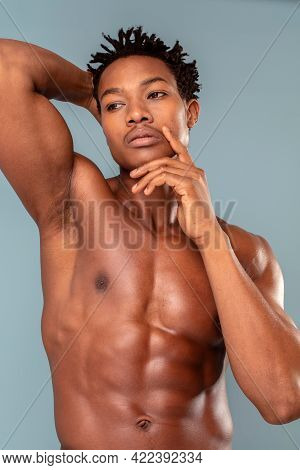 Fit Young Man With Beautiful Torso, Isolated On Blue Pastel Background. The Naked Torso Of African A