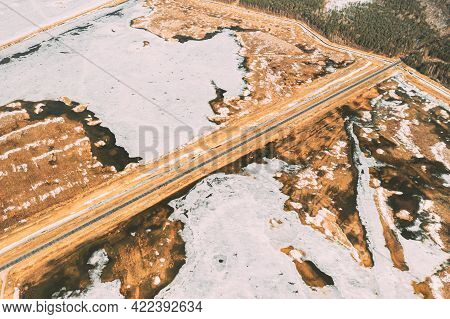 Aerial View Of Road Through Ponds In Winter Snowy Landscape. Frozen Ponds Of Fisheries In South Of B