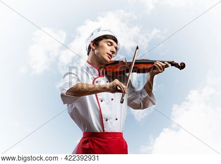 Young Male Chef Playing Violin On Blue Sky Background. Handsome Chef In White Hat And Red Apron Stan