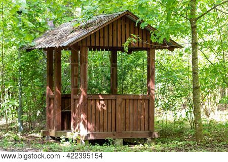 A Wooden Gazebo For Relaxing Stands In The Forest