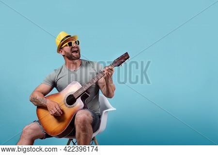 Handsome Bearded Guitarist In Yellow Hat And Sunglasses Sitting On Chair And Singing While Playing O