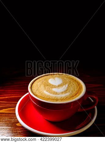 Coffee With Milk Foam Froth Art Served In Red Cup On Desk Dark Background With Copyspace.
