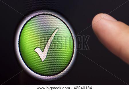 Finger Pressing A Green Tick Button On Touchscreen