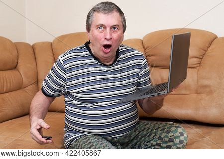 A Freak With A Surprised Face Holds A Laptop In His Hands While Sitting On The Couch. Emotions From