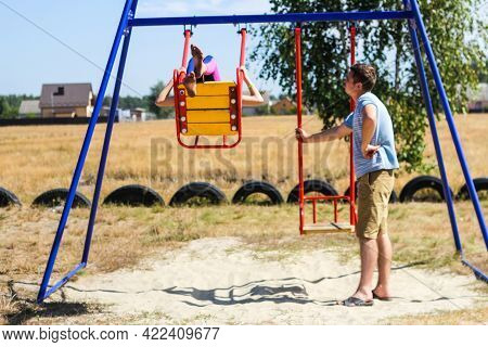 Defocus Little Girl Swinging On Swing On Playground With Young Man, Guy, Her Older Brother. Countrys
