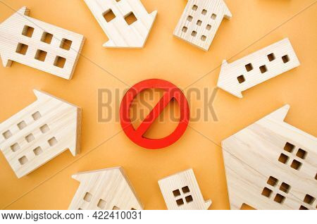 Wooden Houses And A Prohibition Sign. Inaccessible And Expensive Housing. Restrictions And A Ban On