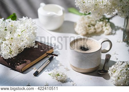 Spring Composition With Cup Of Coffee, Old Book And White Lilac Beautiful Bouquet. Concept Of Spring